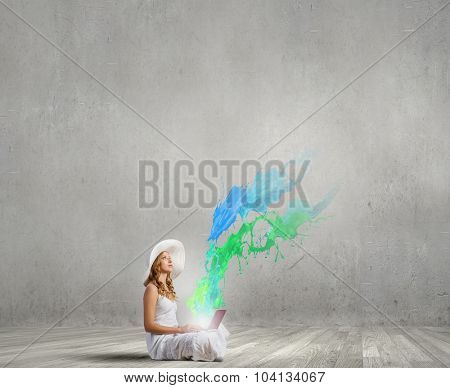 Young lady sitting on floor with laptop on knees