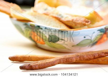 Breadsticks In The Foreground With Bread Inside Bowl In The Background