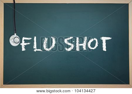 The word flu shot and stethoscope against chalkboard