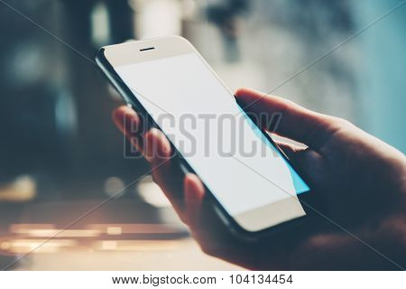 Smart phone in woman's hand. Blured background.