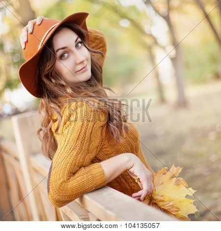 Portrait of the beautiful fashionable woman outdoor on sunny autumn day.