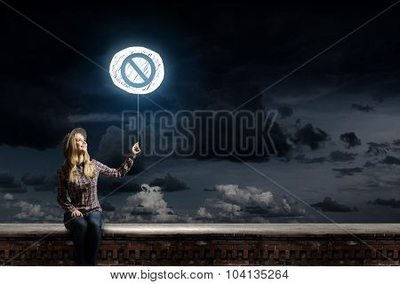 Young woman in casual holding balloon with prohibition sign