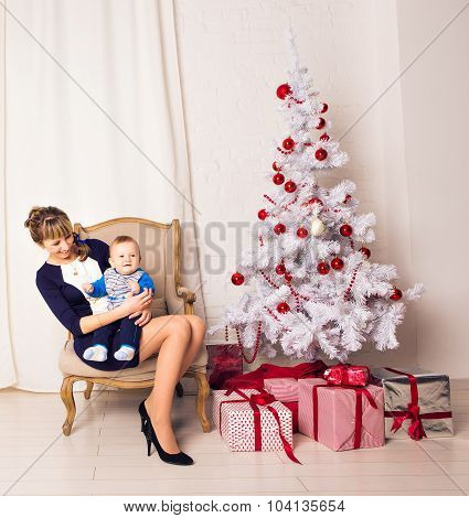 mother and som sitting on  armchair against the Christmas Tree