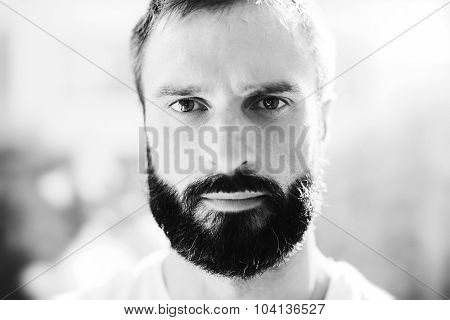BW portrait of a bearded man wearing white tshirt on the blure background and looking