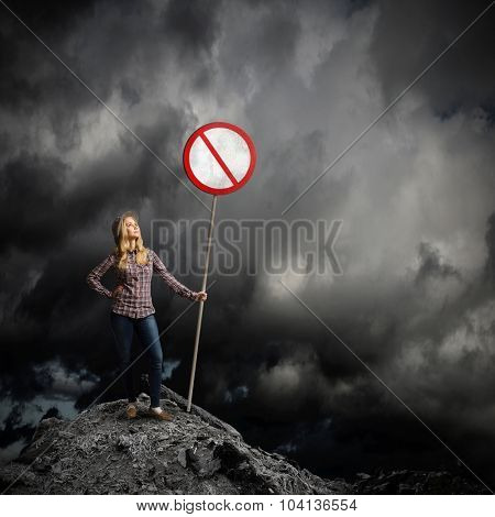 Young girl in casual holding stop sign