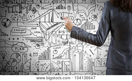 Rear view of businesswoman drawing business sketches on wall