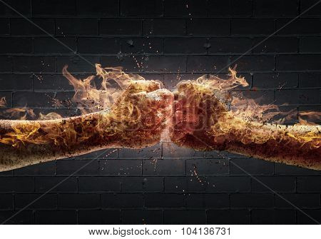 Close up of two fists in fire hitting each other