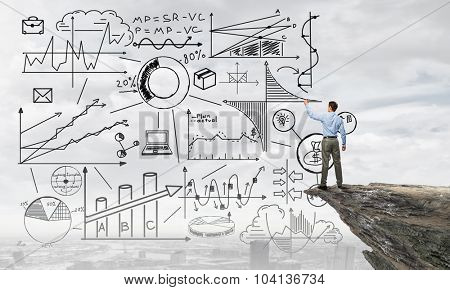 Back view of businessman drawing plan sketches on wall