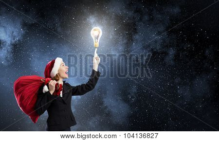 Santa woman with red bag on back pointing on light bulb with finger