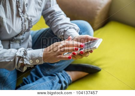 Closeup Of Woman Hands Using Mobile Phone At Home