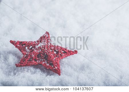 Beautiful magical vintage red star on a white snow background. Winter and Christmas concept.