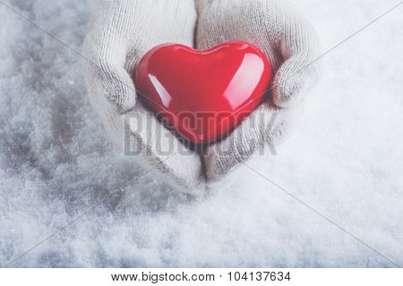 Female hands in white knitted mittens with a glossy red heart on a snow winter background. Love and St. Valentine cozy concept.