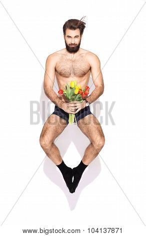 A Young Man With A Beard And Flowers Jumping In The Studio On A White Background