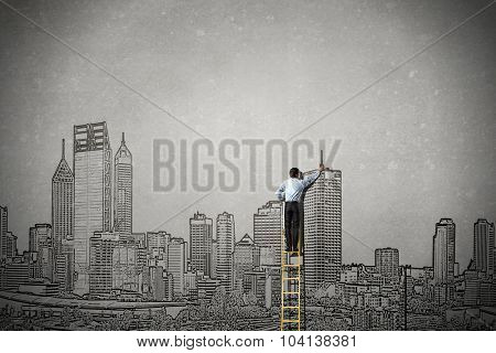 Rear view of businessman standing on ladder and drawing buildings