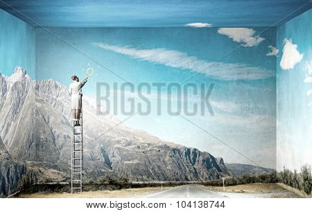 Businesswoman standing on ladder and drawing on wall