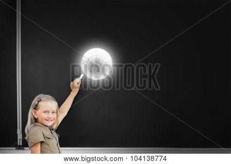 Cute school girl drawing moon on blackboard