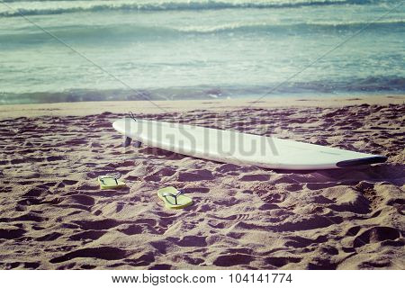 Surfboard And Flip Flops On The Sand