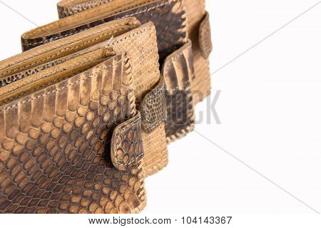 Several Of Snake Skin Purse On A White Background
