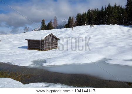 Wooden Hut On Snow Meadow