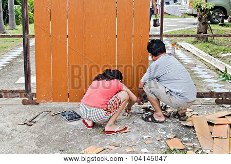 A Man And His Daughter Repairing The Gate