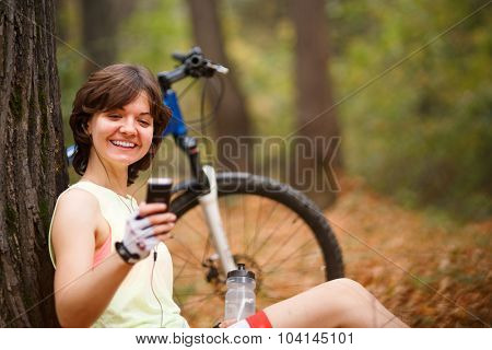 Young brunette woman with mp3 player sitting in city park