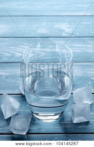Glass Of Water And Melting Ice Cubes On A Wooden Table.