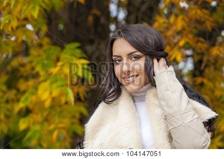 Portrait of young Italians in beige coat against the background of the autumn park
