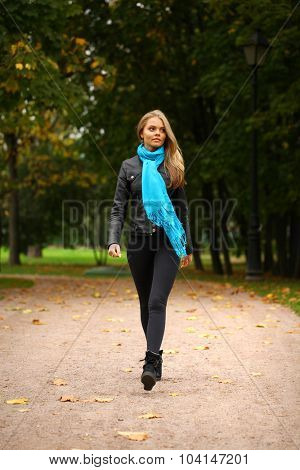 Portrait in full growth of young beautiful blonde women walking, on background autumn park