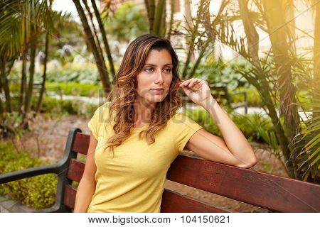 Pensive Woman Sitting On Park Bench