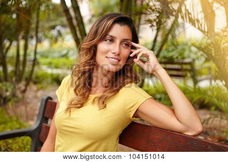 Smiling Lady Sitting On Bench With Hand In Hair