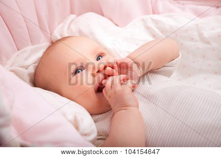 Cute three month baby girl laying in a bassinette