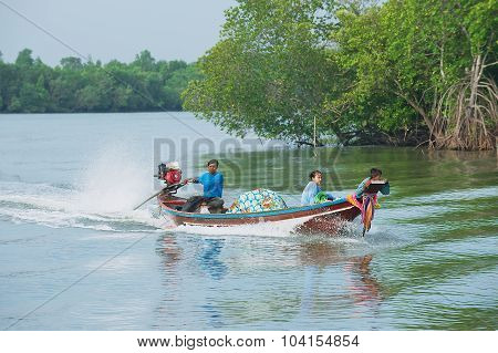 Thai man rides long tail motorboat with his family in Tha Thong, Thailand.