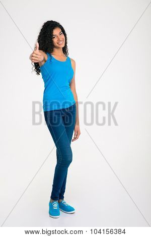 Full length portrait of a happy african woman showing thumb up isolated on a white background
