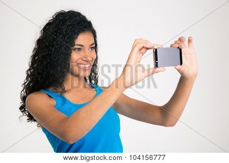 Portrait of a smiling afro american woman making selfie photo on smartphone isolated on a white background