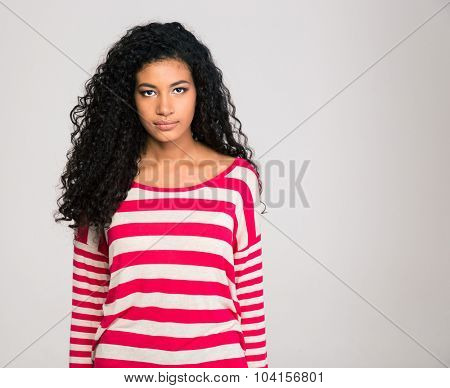 Portrait of a serious afro american woman looking at camera isolated on a white background