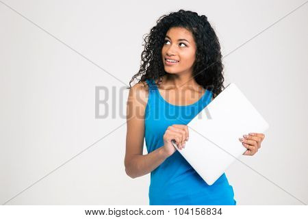 Portrait of a happy afro american holding laptop and looking away on copyspace isolated on a white background