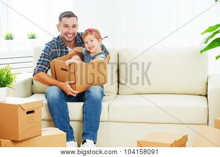 Happy Family Moves To New Apartment. Dad And Child  Daughter With Cardboard Boxes