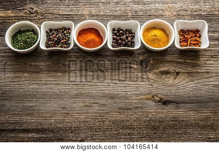 aromatic spices in bowls in horizontal row on wooden background