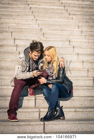 Hipster Couple In Love Having Fun With Smartphone - Modern Concept Of Connection In A Relationship
