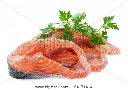 Two pieces of salmon fillet with a sprig of parsley on a white background