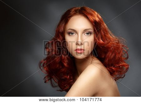 Portrait Of A Young Ginger Woman On A Dark Background.