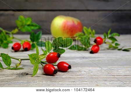Rosehips With Apple On An Old Wooden Table