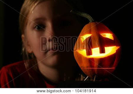 Young girl with Halloween pumpkin jack-o-lantern
