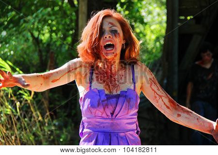 MUSKOGEE, OK - Sept. 12: A young woman dressed as a zombie scares athletes during the Castle Zombie Run at the Castle of Muskogee in Muskogee, OK on September 12, 2015.