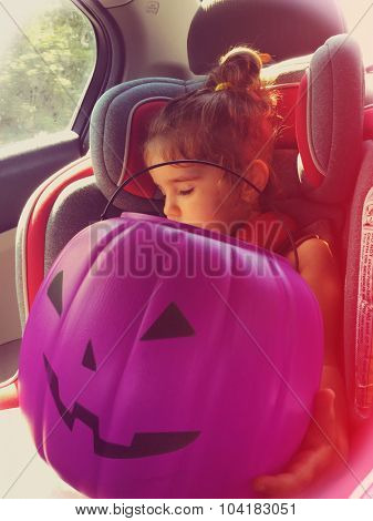 Authentic image of a toddler girl asleep in a car seat with a plastic Halloween pumpkin - Instagram filter