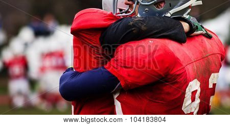 american football game - players hugging on field