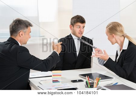 Two Businesspeople Quarreling To Young Businessman