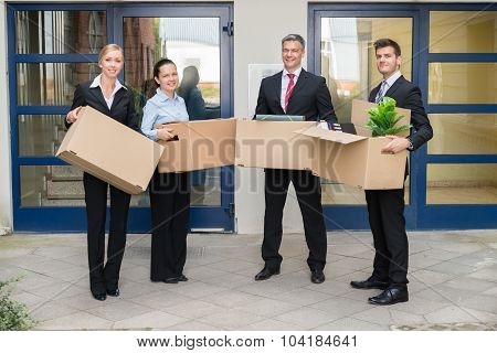 Businesspeople With Cardboard Box Moving Into New Office