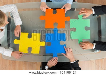 Businesspeople With Jigsaw Pieces At Desk