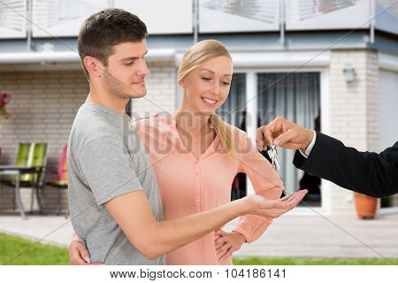 Agent Giving Key To Young Couple